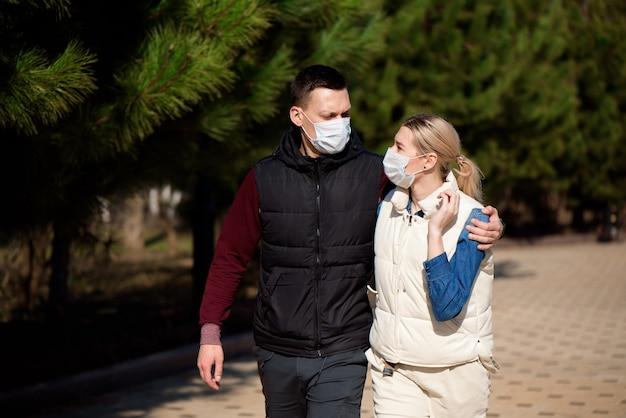 医療用マスクを着用して公園を一緒に歩いているカップル