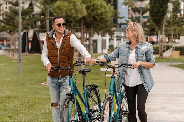 밖에 서 그들 옆에 자전거와 함께 산책하는 커플