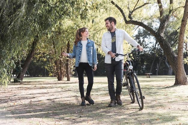 Пара, идущая с велосипедом в парке