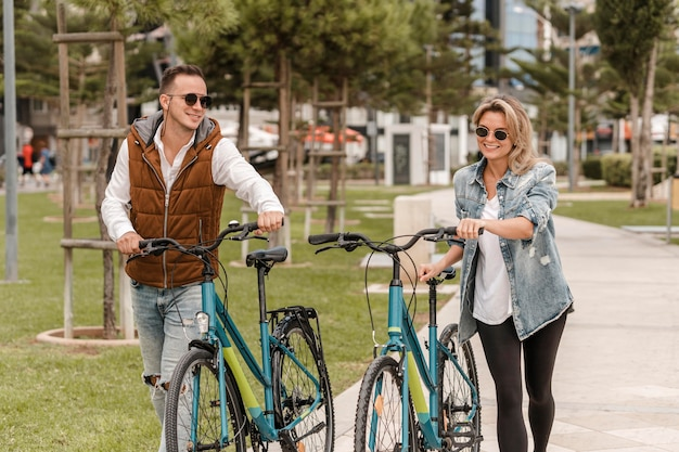 Couple walking with a bike next to them outside