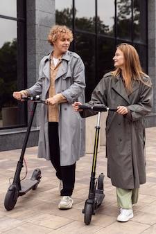 屋外で電動スクーターと一緒に歩くカップル