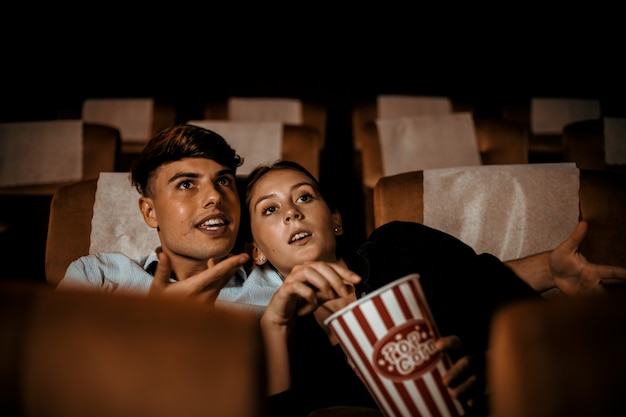 Couple watch movie in theater with popcorn smile and happy face