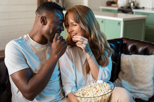 Пара смотрит фильм во время еды попкорна