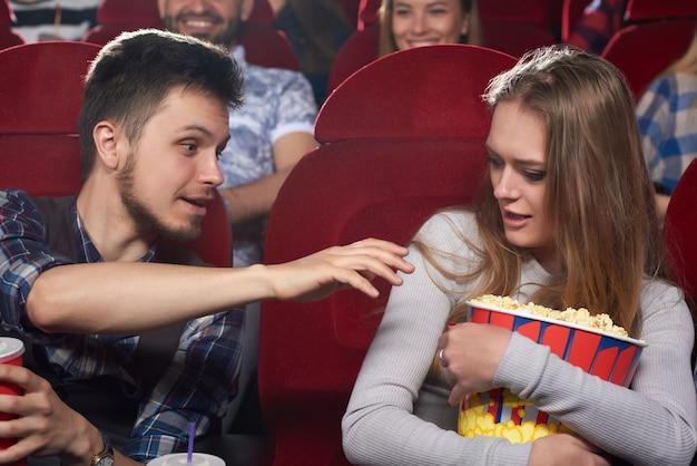 Пара смотрит фильм в кино, сердитый парень тянет руку к попкорну, а его жадная подруга обнимает большое ведро и кричит.