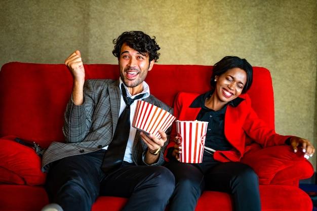 Пара смотрит фильм, чувствуя себя счастливым и расслабляющимся в кинотеатре