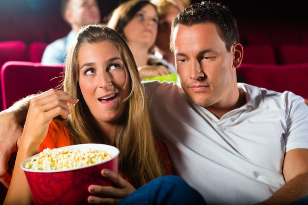 Couple watching movie at movie theater and eating popcorn