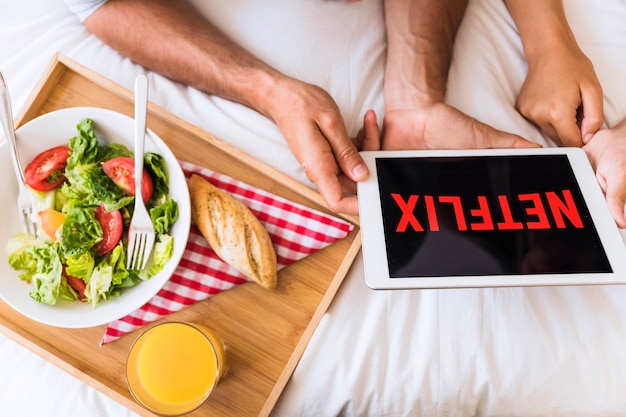Couple watching netflix shows near salad
