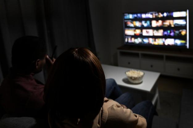 Пара смотрит netflix вместе дома в помещении