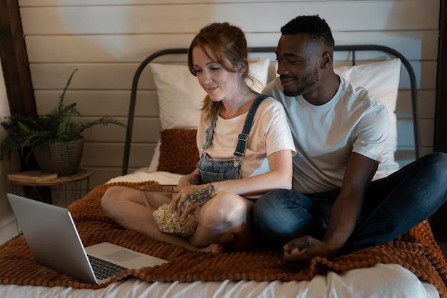 Пара вместе смотрит netflix в спальне