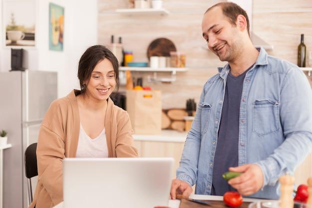 野菜サラダのためにキッチンのラップトップでオンラインレシピを見ているカップル。男性は女性が健康的なオーガニックディナーを準備するのを手伝い、一緒に料理をします。ロマンチックな陽気な愛の関係
