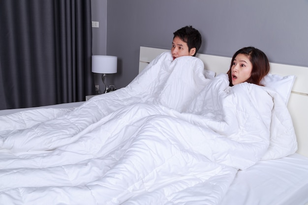 Couple watching scared movie under the blanket on bed