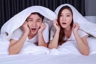 ベッドで毛布の下で怖い映画を見てカップル