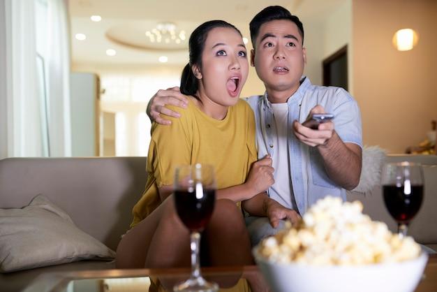家で怖い映画を見ているカップル
