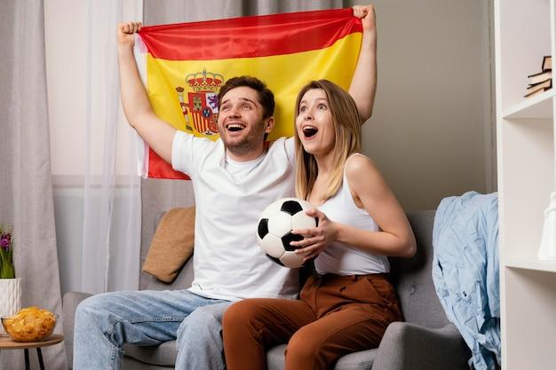 Пара смотрит спортивную программу по телевизору