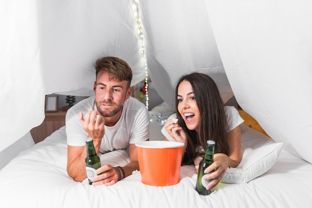 Couple watching television lying on bed enjoying popcorn and alcohol drink