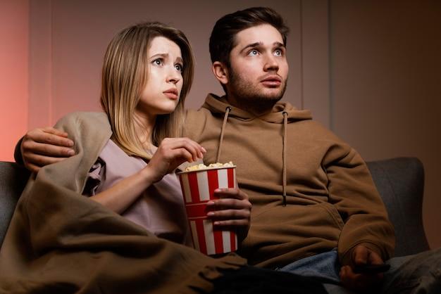 Пара смотрит телевизор и ест попкорн