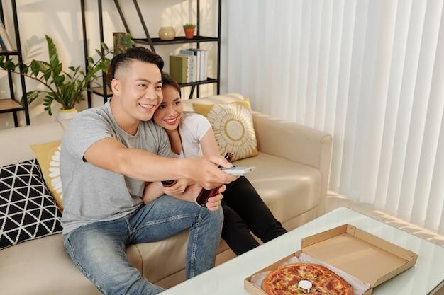 自宅でテレビを見ているカップル