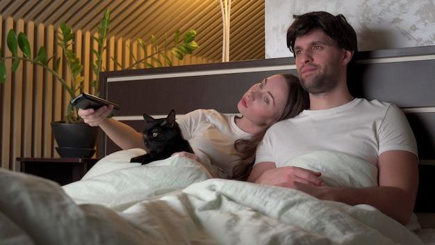 침대에 누워 집에서 밤에 tv를 시청하는 커플.