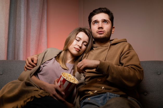 Couple watching tv and eating popcorn