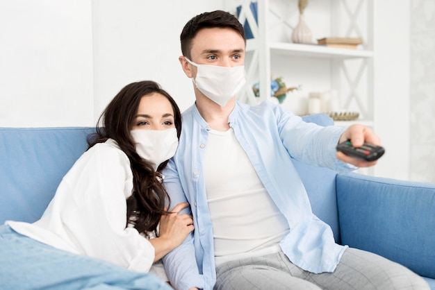 Couple watching tv at home with face masks
