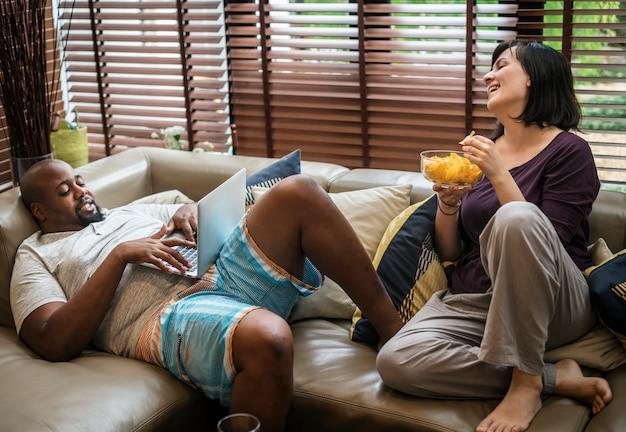 Пара смотрит телевизор на диване