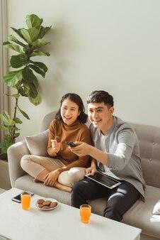 自宅のリビングルームのソファに座ってテレビを見ているカップル。男性はザッピングをしていて、女性はタブレットを持ってあなたを見ています