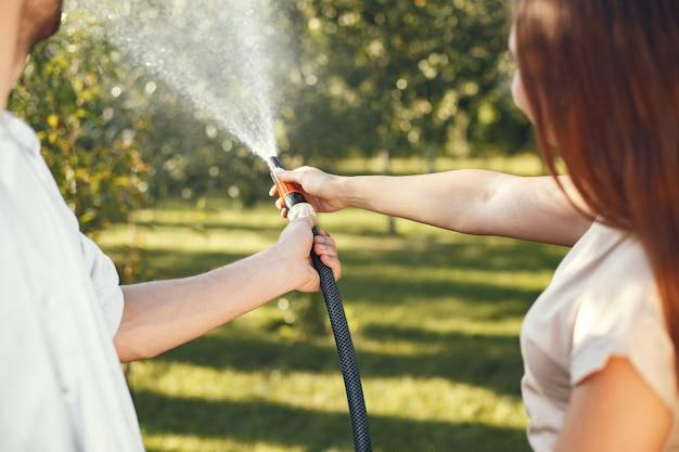彼の庭で彼の植物に水をまくカップル。青いシャツを着た男。家族は裏庭で働いています。