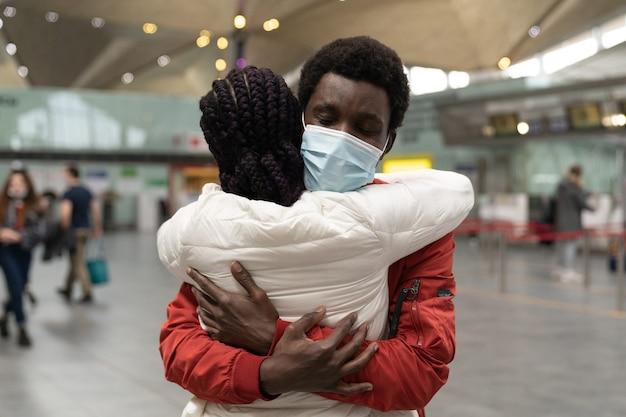 カップルは空港ターミナルで新しい正常性の範囲内でお互いを抱き締めるフェイスマスクを着用します