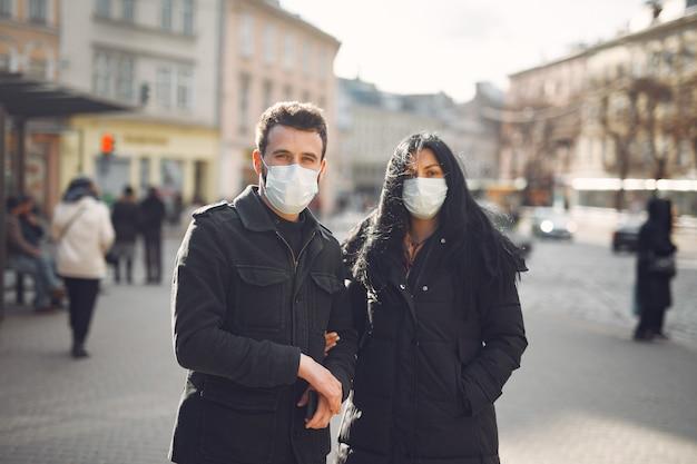 通りに立っている防護マスクを着ているカップル