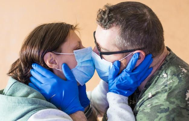 ウイルスのフェイスマスクとキス保護手袋を身に着けているカップル。コロナウイルスのコンセプト