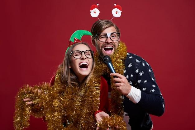 La coppia che indossa abiti natalizi si diverte molto mentre si esibisce al karaoke