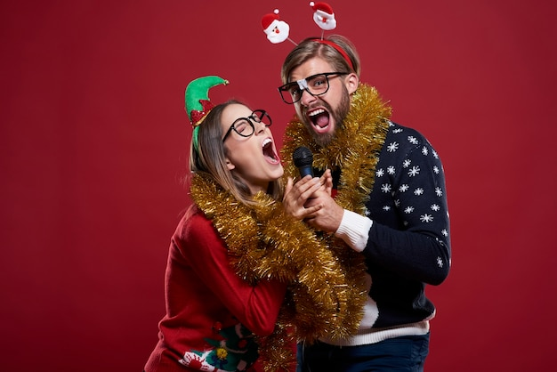 Couple wearing christmas clothes has great fun while having karaoke performance
