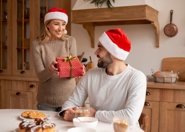 Couple wearing christmas hats indoors