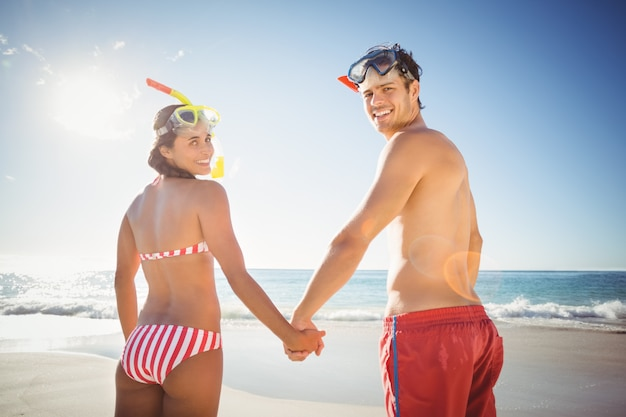 Couple wearing diving mask standing on beach