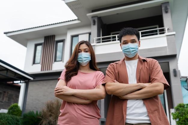 自宅でコロナウイルス(covid-19)を保護するためのフェイスマスクを着用しているカップル