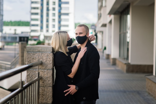 Couple wearing fashionable protective masks, walking in empty street of the city during quarantine
