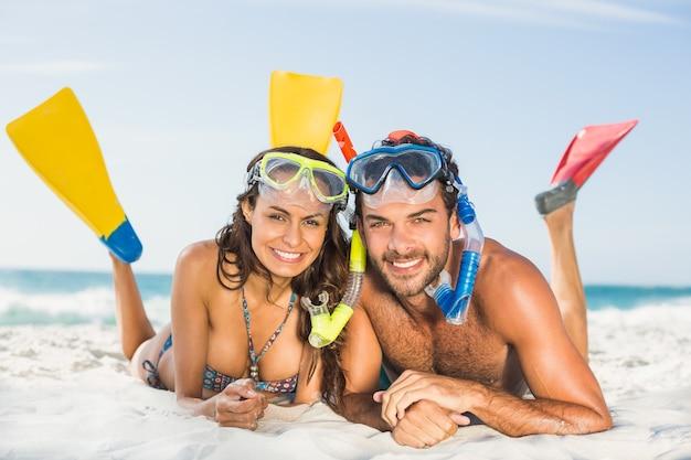 해변에서 오리발을 착용하는 커플