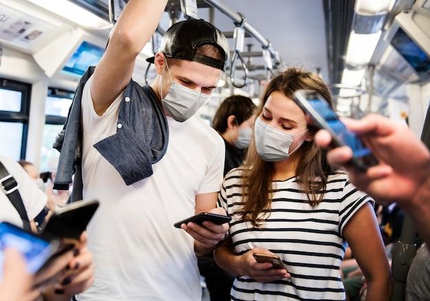 新しい通常の公共交通機関で旅行中に電車の中でマスクを着用しているカップル