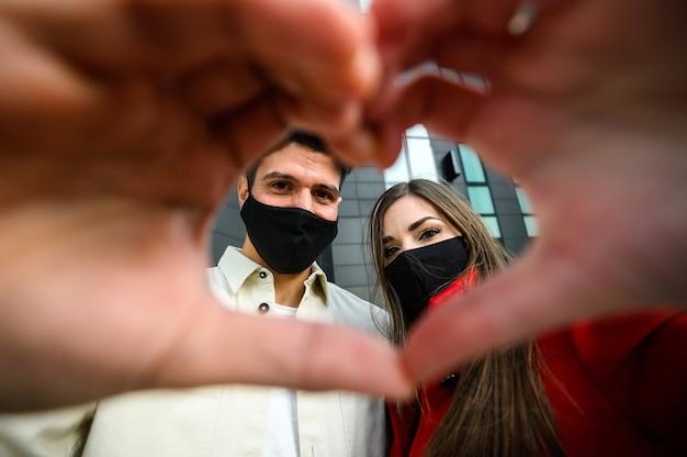 마스크를 쓰고 심장, 코비드, 코로나바이러스 개념의 표시를 만드는 커플