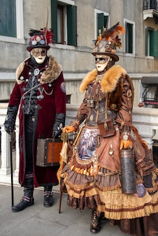 Couple wearing ornate matched carnival costumes posing for picture by city, italy, venice