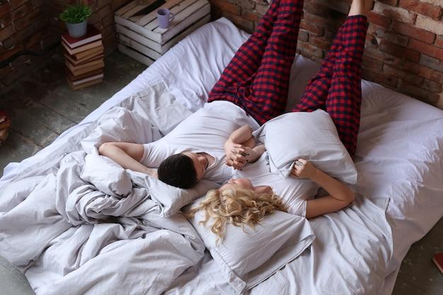 パジャマを着て、ベッドで寝ているカップル
