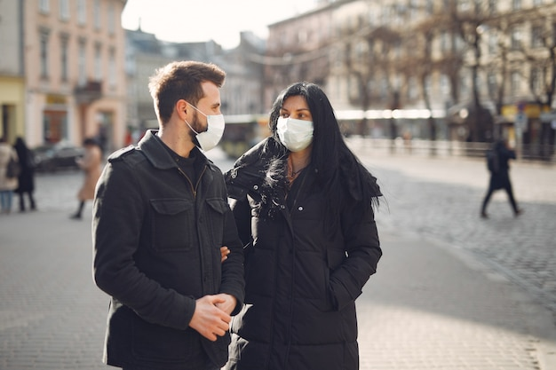 Couple wearing a protective mask standing on the street