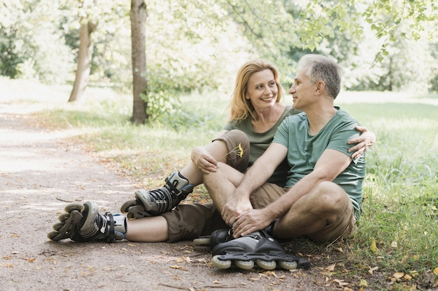 Couple wearing roller skates sitting on the grass