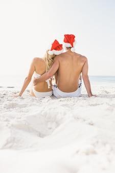 Пара в шляпе санта-клауса на пляже