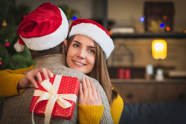 Couple wearing santa hats hugging eachother