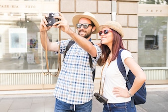 Couple wearing sunglasses and hat taking selfie on camera