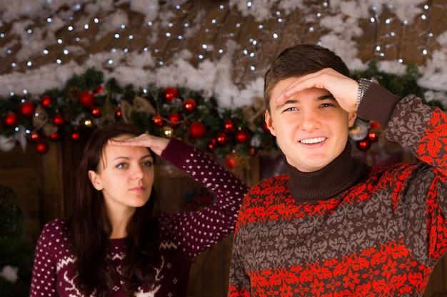 ログキャビンの前で冬の屋外の距離を見てセーターを着ているカップル