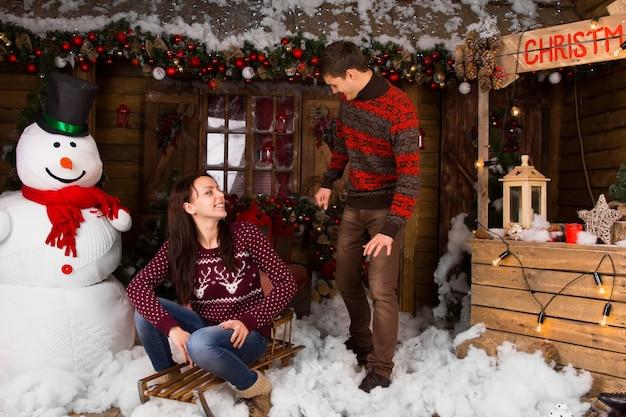 통나무집 앞 겨울에 야외에서 썰매와 스웨터를 입은 커플