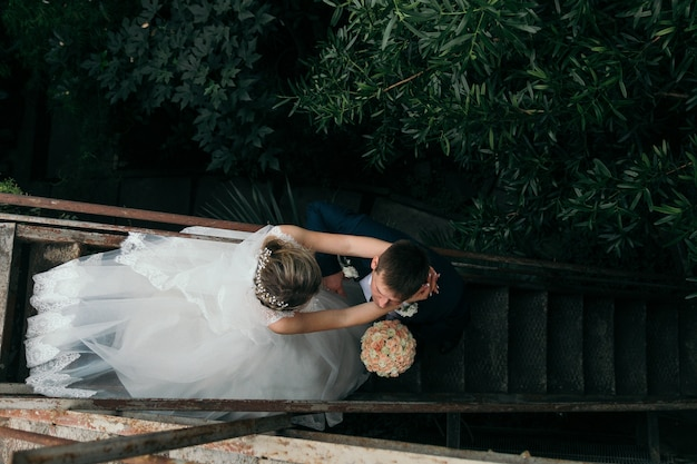 Couple on wedding day on the park on the stairs. top view. marriage. unrecognizable.