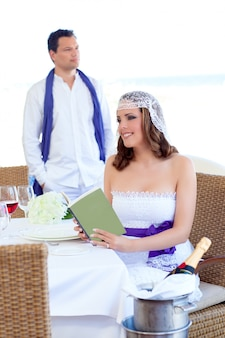 Couple in wedding day woman reading book on banquet